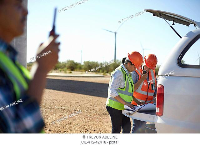 Engineers reviewing blueprints at truck at sunny wind turbine power plant
