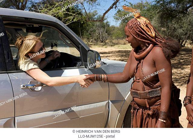 Close up of women greeting each other, Epupa Falls area, Kaokoland, Namibia
