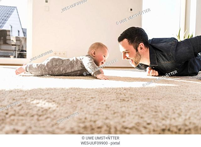Father and baby son playing crawling on carpet