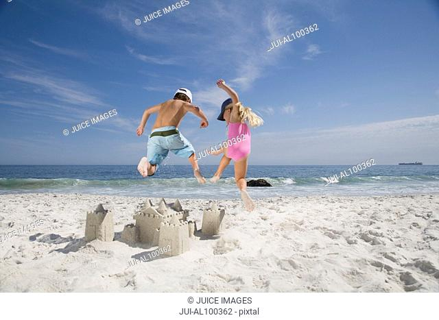 Brother and sister jumping on sandcastle on beach