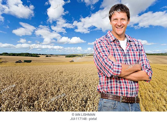 Portrait Of Farmer Standing In Wheat Field At Harvest