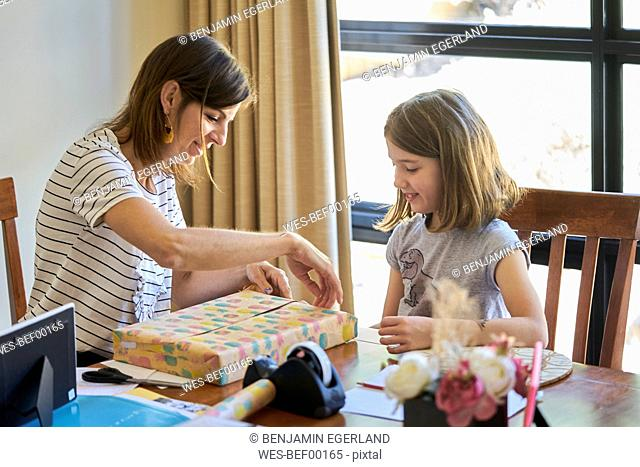 Mother and daughter packing gift at table at home
