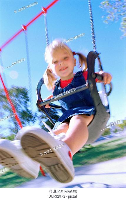 Girl swinging on playground swing