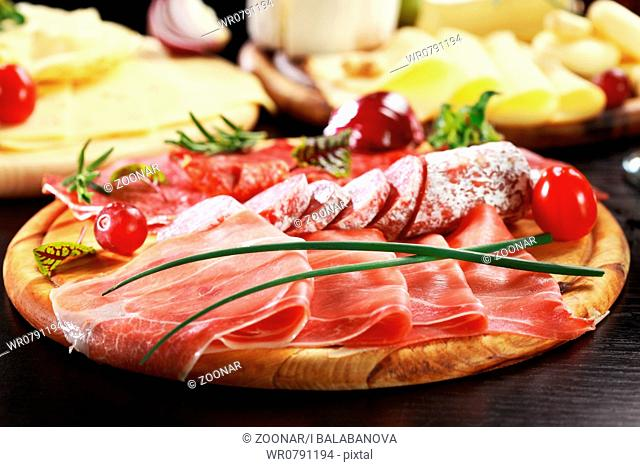 Salami and cheese platter with vegetable and herbs