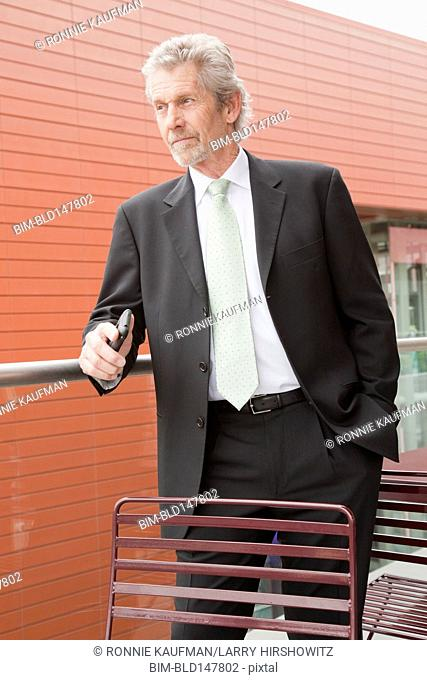 Caucasian businessman holding cell phone outdoors
