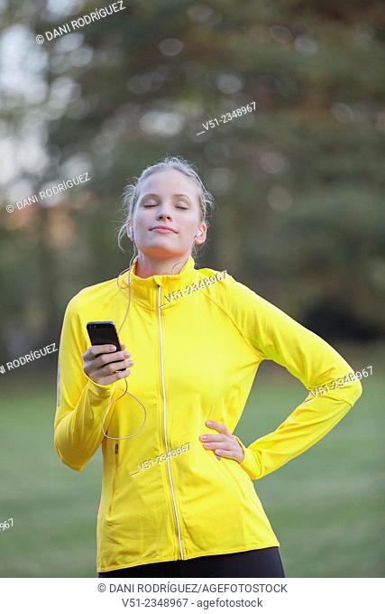 Blonde woman doing sport in park and listening to music with eyes closed