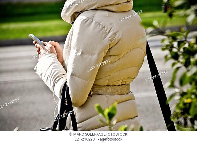 Woman using smartphone outdoors. Barcelona, Catalonia, Spain