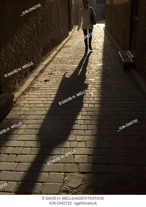 Silhouette of woman walking on cobblestone in Fez, Morrocco