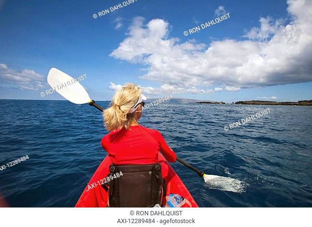 Woman kayaking in South Maui with West Maui Mountains in the background; Makena, Hawaii, United States of America