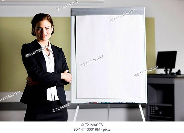 Woman standing next to a white board