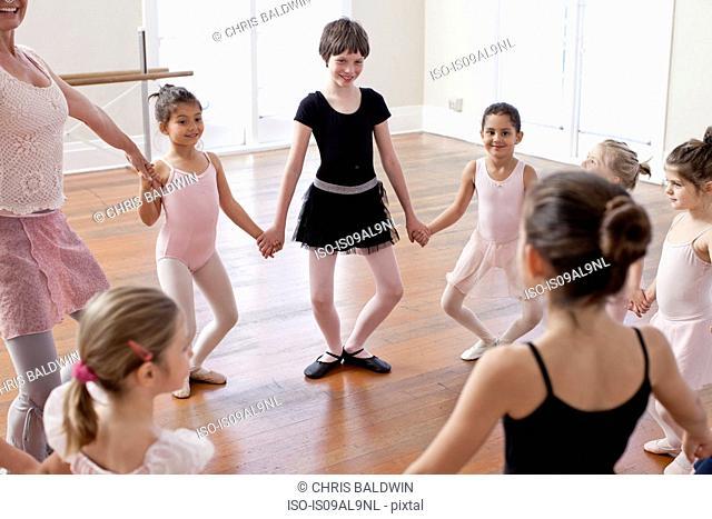 Children and teacher in a circle practicing ballet in ballet school