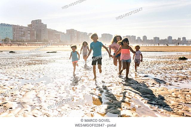 Group of six children running together on the beach