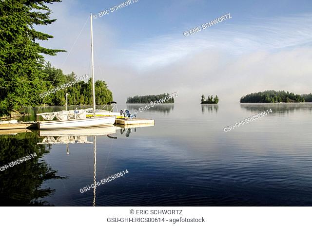 Boats Parked by Dock on Lake with Clearing Fog in Distance