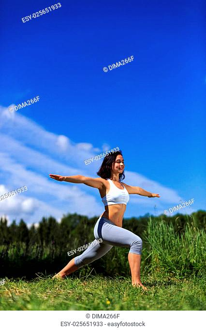 girl doing yoga outdoor with closed eyes and smiling, vertical