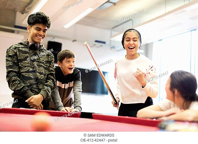 Happy teenagers playing pool in community center
