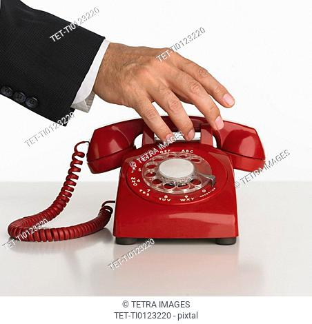 Close up studio shot of man reaching for rotary telephone