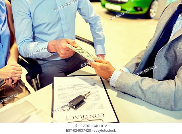 auto business, sale and people concept - close up of customers giving money to dealer and buying car in auto show or salon