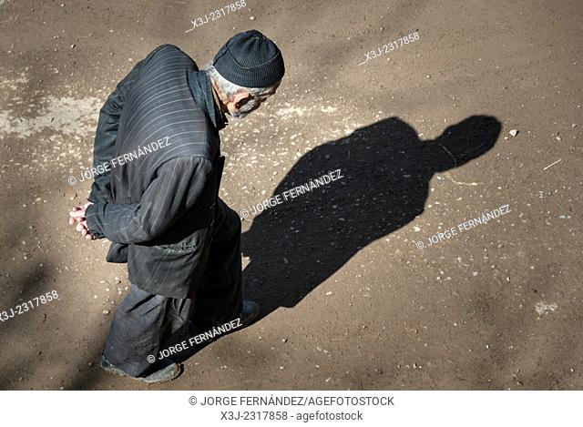 Old man walking thoughful in the street, Alamut, Iran