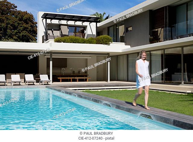 Woman walking along luxury swimming pool