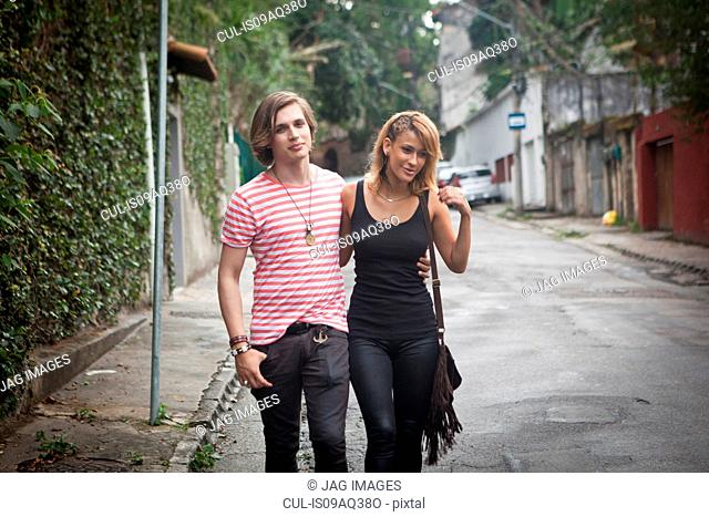 Young couple strolling along suburban street