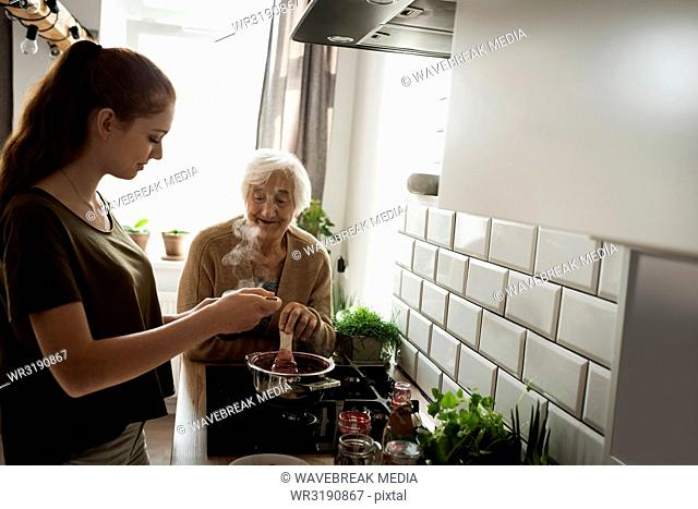 Grandmother and grand daughter cooking in the kitchen