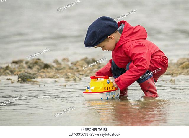 small boy playing with his plastic bright yellow and red tug boat in the shallow ocean water