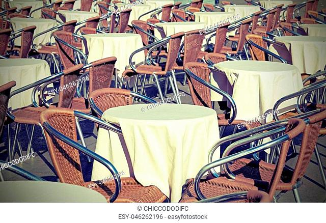 Many tables of an alfresco bar with lots of chairs and vintage effect