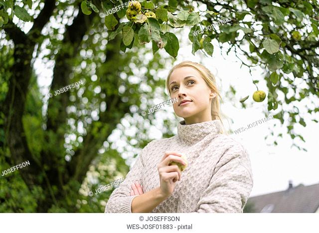 Portrait of young woman at apple tree in garden