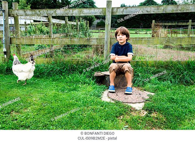 Boy sitting on farm with chicken