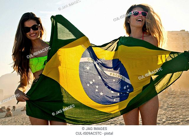 Two young women having fun on beach with Brazilian Flag