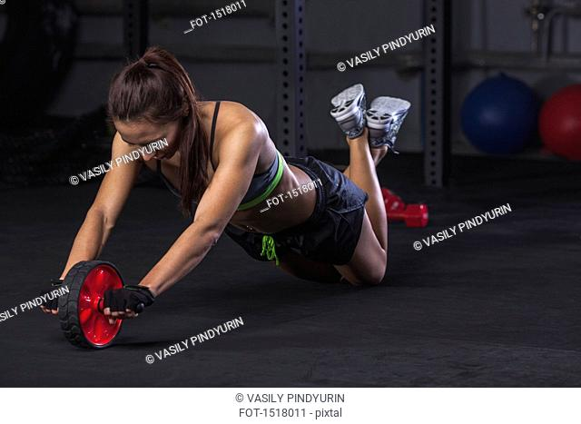 Young woman exercising with wheel at gym