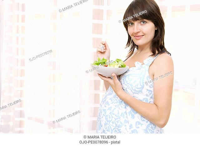 Pregnant woman eating bowl of salad
