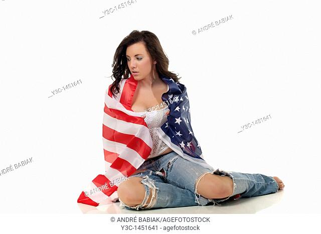 Young woman in teenager outfit wrapped in american flag