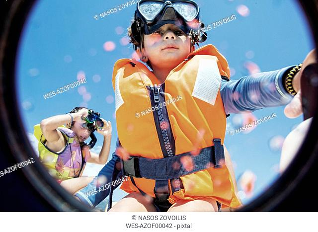 Toddler wearing life jacket and diving goggles with brother in background