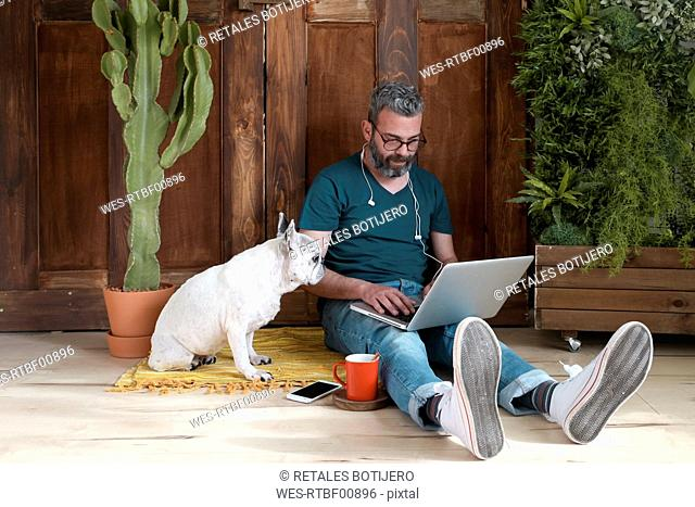Bearded man sitting with his dog on the floor at home using laptop