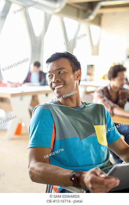 Happy casual businessman looking over shoulder in office