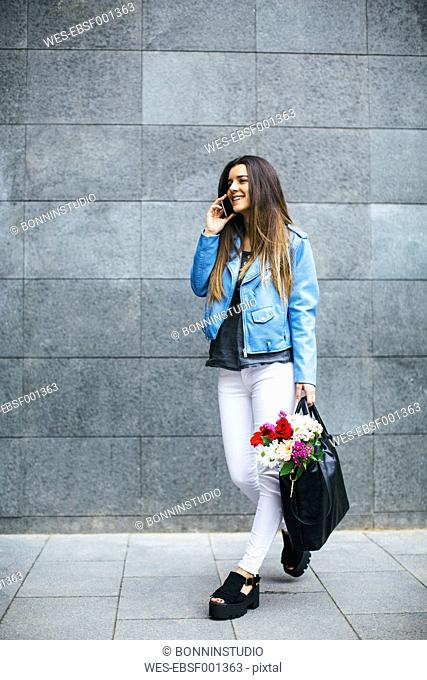 Young woman on cell phone with bunch of flowers in her bag