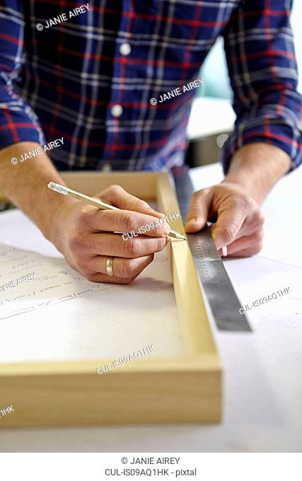 Close up of mid adult man measuring frame on workbench in picture framers workshop