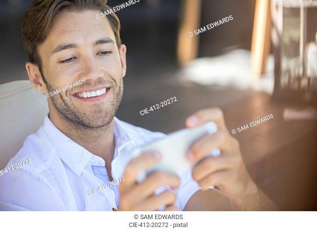 Man using cell phone in armchair