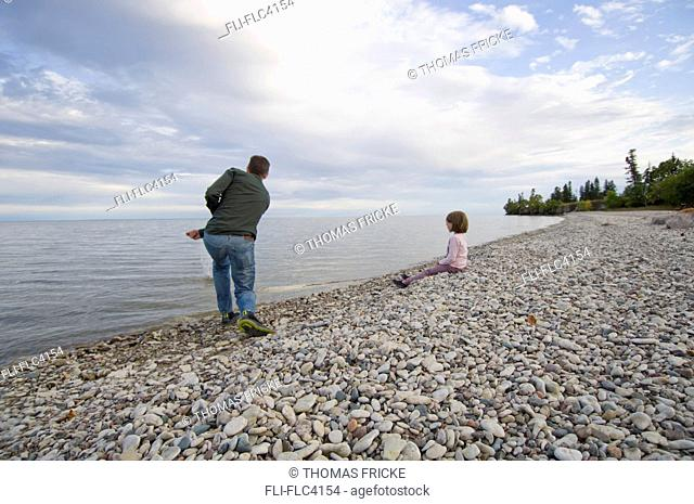 Father and young daughter on rocky shores of Lake Winnipeg, Hecla Island, Manitoba, Canada