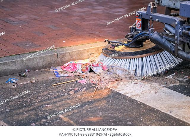 01 January 2019, Germany (German), Hannover: A sweeper sweeps together burned fireworks and other remains of New Year's Eve on Lister Platz