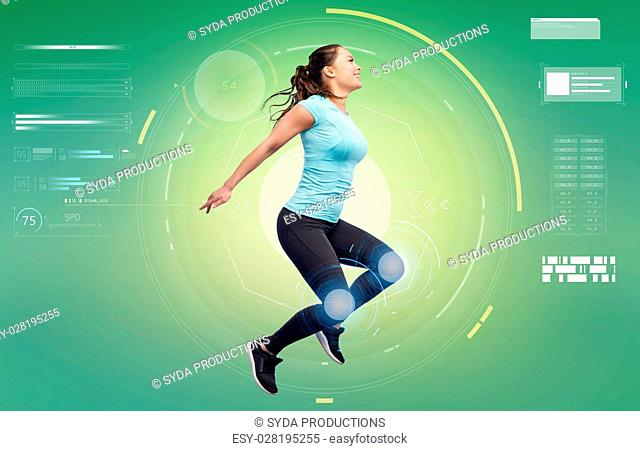 sport, fitness, motion, technology and people concept - happy smiling young woman jumping in air over white background