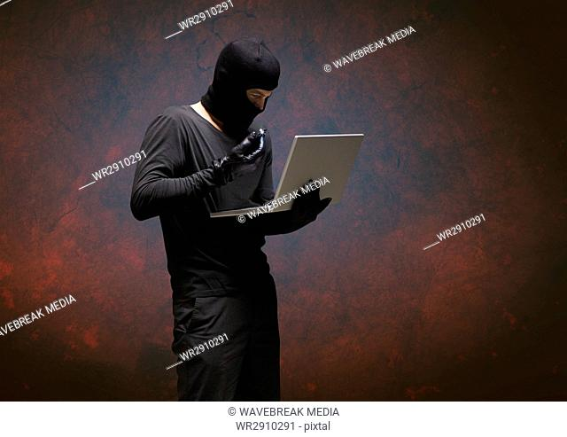 Criminal with laptop against dark background