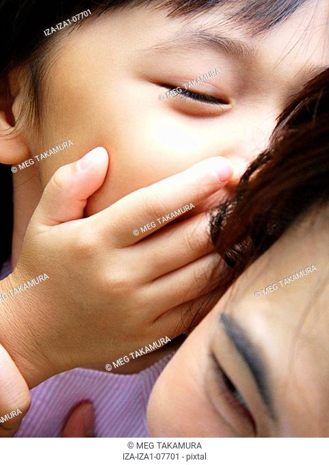 Close-up of a girl whispering into her mother's ear