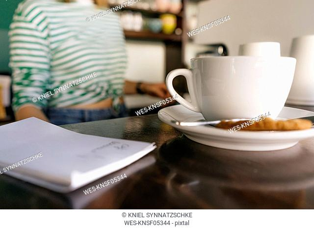 Cup of coffee and notepad on table in a cafe with woman in background