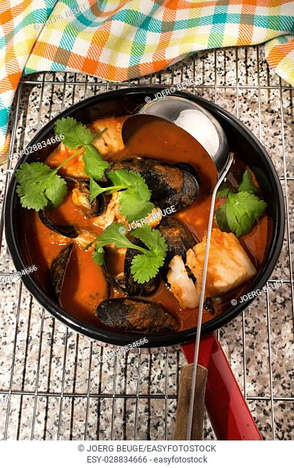 mussels, cod and tomato soup in pot