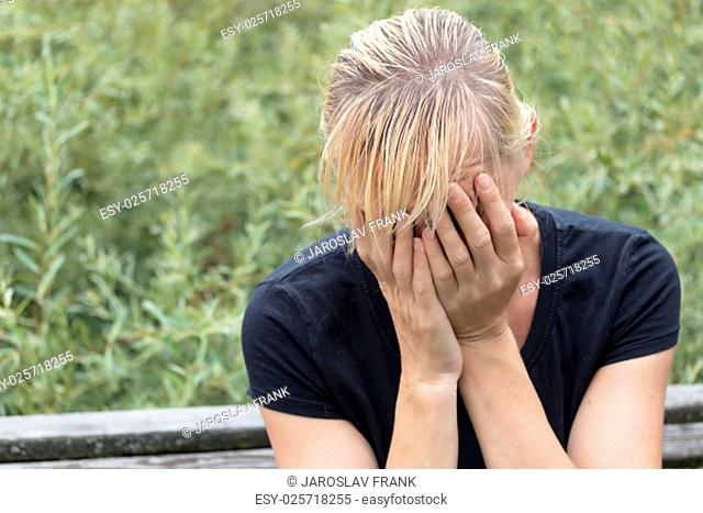 Desperate blonde middle aged woman in black shirt is sitting on the bench outside. Hands are covering her face