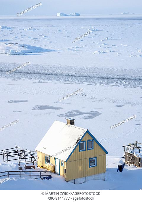 Sea ice in the frozen Disko Bay with icebergs. Town Ilulissat at the shore of Disko Bay in West Greenland, center for tourism, administration and economy