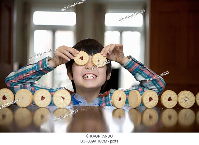 Boy playing with biscuits