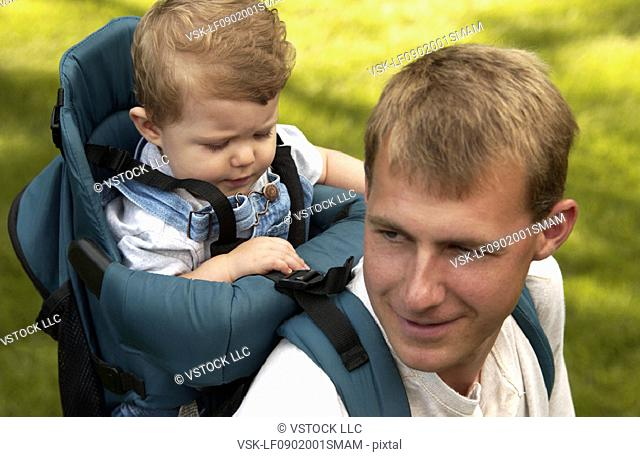 Father carrying son in backpack hiking on walk